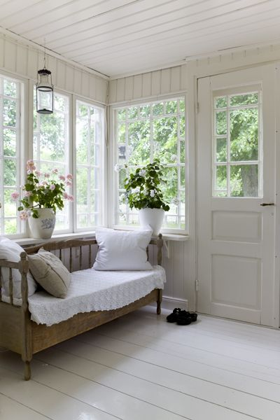 Traditional Swedish glassed porch with wooden sofa