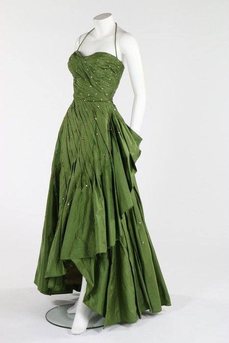 Early '50s Norman Hartnell green taffeta ball gown with strapless boned bodice, a spiral of graduated pleats with flounced graduated hem, and studded overall with copper and silver facetted beads.