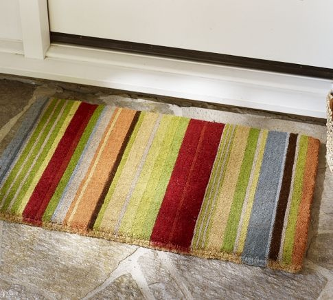 A colorful striped door mat is so welcoming