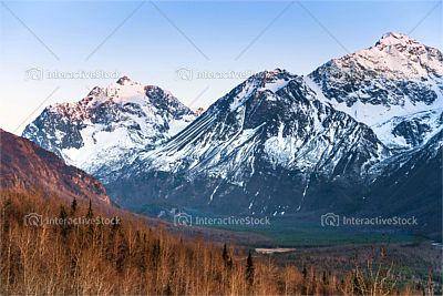 Góry przykryte śniegiem nad zieloną doliną. Natura piękne maluje obrazy.