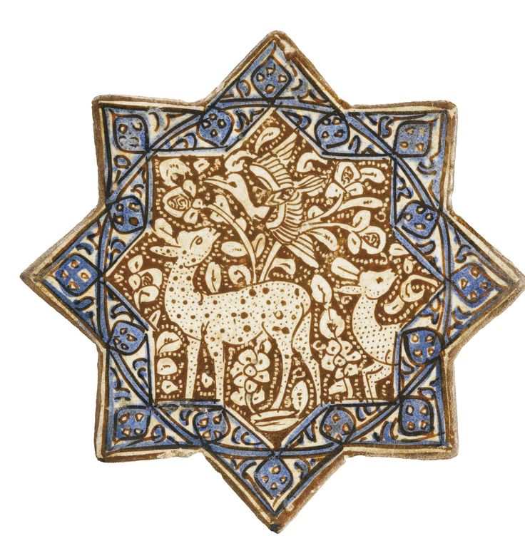 A Kashan lustre pottery star tile with gazelles in foliage, Persia, 14th century of eight-pointed stellar form, decorated in lustre over an opacified tin glaze with inglaze cobalt blue, featuring two gazelles within a foliiate background with a bird flying above, border with stylised blue design, old collection label to reverse '59' 20.3cm.