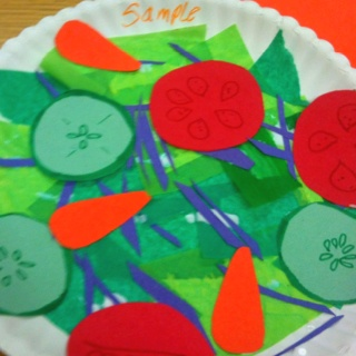 Salad craft: green tissue paper, paper cucumbers, carrots, tomatoes and cabbage