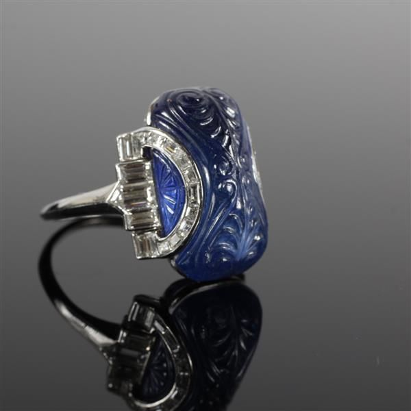 Art Deco platinum minimum 15ct. carved sapphire cabochon and diamond ring. Believed to be a natural corundum sapphire, 19.5 x 10.5 x 9.1mm. Contains two shield cut and baguette diamonds. Marked 2033x9597 IRID PLAT. 7.1 dwt<br> Size 8