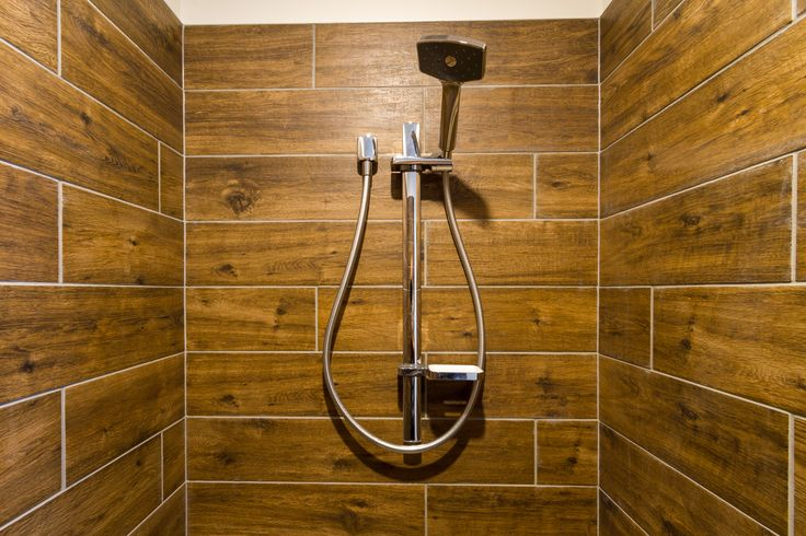 Wooden look in this ensuite shower, is also used as a head board for the master bed