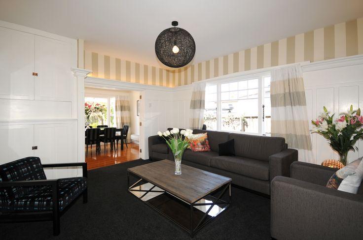 White Wooden Paneling, heritage stripe wall paper, dark carpet.