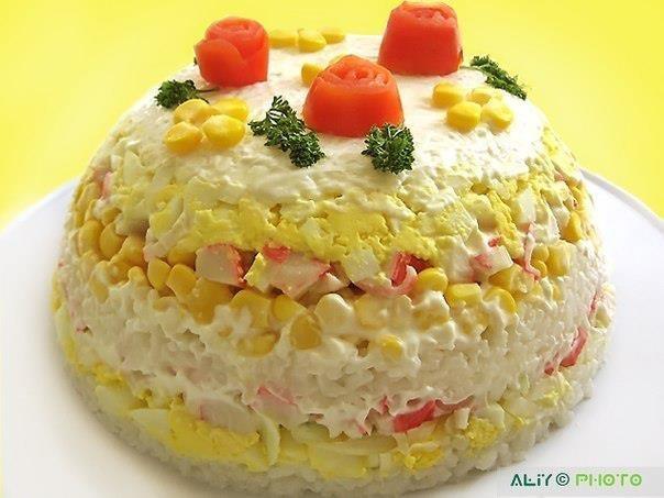 чуть больше половины стакана риса 200 г кр палочек  1 б. конс кукурузы  5 яиц 1 луковица   Отложим немного кукурузы для украшения. розочки сделаны из шкурки помидора 2. 1/3 часть риса , Каждый слой хорошо приминаем,3. половина яиц, 4. Половина кр палочек, 5. Всю кукурузу, 6. еще 1/3 часть риса,   7. Оставшиеся крабовые палочки, . Весь лук,   8. Оставшиеся яйца,   9. Оставшийся рис. Сверху ставим блюдо, на котором будет лежать салат. И переворачиваем. Чашку снимаем.