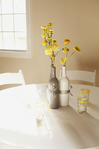 Yellow flowers in silver and white wine bottles DIY centerpiece