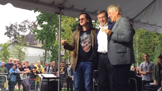 Mayor John Tory (middle) puts his arms around Rush band members Geddy Lee (left)…