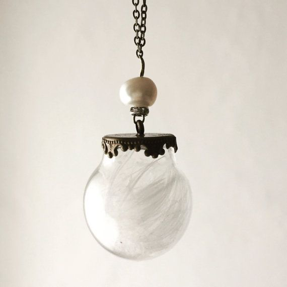 Catena in ottone anticato con sfera in vetro soffiato contenente semi di tarassaco o sabbia e conchiglie.  Il ciondolo è appeso alla catena assieme ad un cristallo di vetro e accanto ad esso tintinna un ramoscello in ottone.  La versione più romantica e natalizia, con Ciondolo riempito di perline dorate e perle di fiume appese sopra la Boule di vetro.  Disponibile anche la versione con catena sottilissima color bronzo, perle di fiume e ciondolo con piuma doca.   È possibile personalizzare…