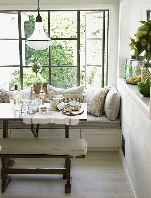 window seat built into the corner instead of a table & chairs, simple box benches finished with molding to create panels. Kitchen? I wonder how dirty the cushions would get?
