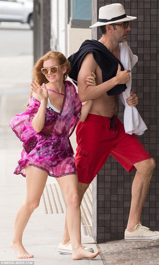 Beaming barefoot beauty: Isla Fisher (left) smiled and waved at locals in Sydney as she strolled around barefoot on Wednesday with her husband Sacha Baron Cohen (right)