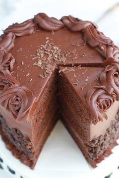 Ultimate Triple Chocolate Layer Cake - Super decadent and moist triple layer chocolate cake with a fluffy milk chocolate frosting covered with mini chocolate chips. The perfect cake for celebrating a birthday or any special occasion.