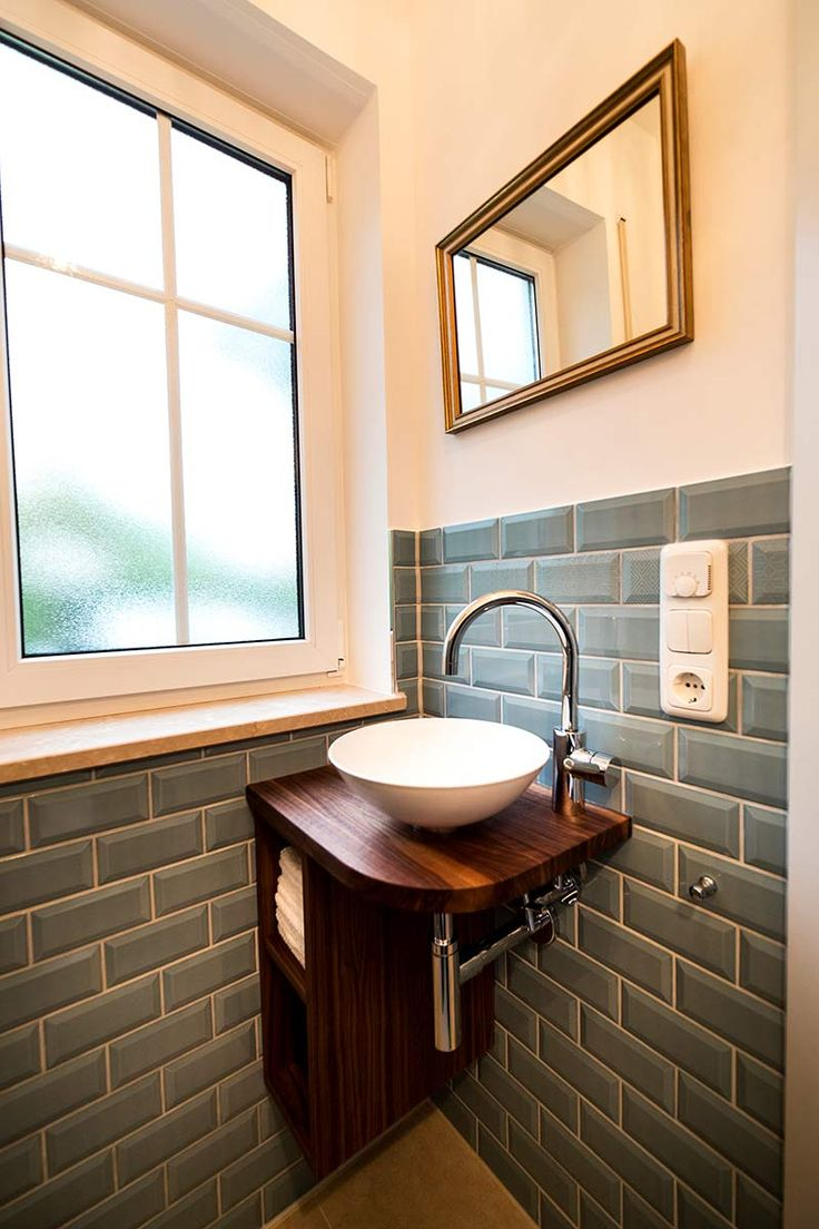 Mini-Waschtisch Gäste-WC aus Holz mit kleinem Regal, weiße Aufsatzschale, halbhoher Fliesenspiegel aus Retro-Fliesen in Wasserblau, übrigen Wandabs…