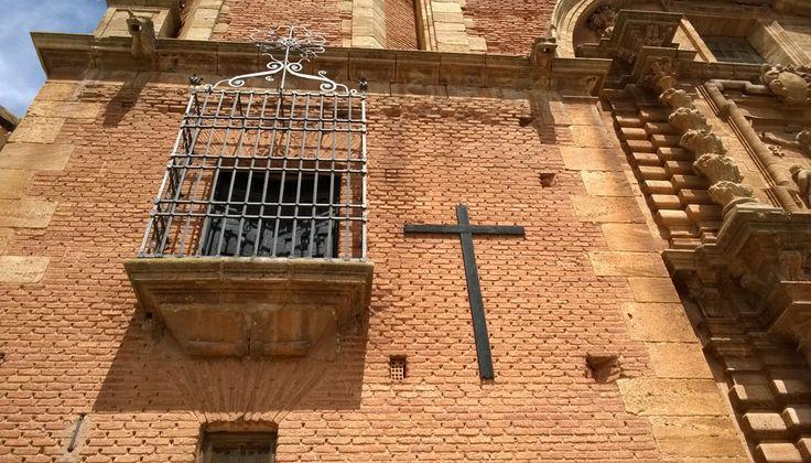 Una sencilla cruz de madera está clavada en la fachada frontal de la Catedral de San Carlos del Valle, La Mancha