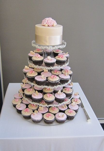 Beautiful wedding cupcake display. Cupcakes on all tiers except the top, with a cake to preserve the tradition of cutting the cake together.