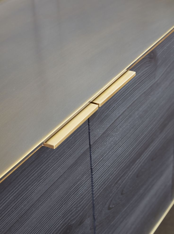 Custom warm brass hardware and darkened bronze metal top bring luxe finishes and elegance to this wall hanging credenza.