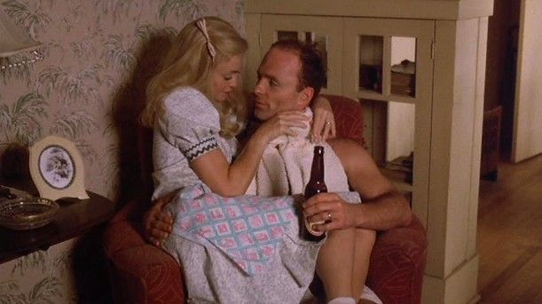 "Goldie Hawn & Ed Harris in ""Swing Shift"" - in the corner of the living room at the beginning of the movie, in one of their overstuffed chairs, showing a portion of the half-collonade with the glass doors for displaying china, glassware, books, nik-naks, etc. There's a matching one on the other side of the living room separating it from the dining room also."
