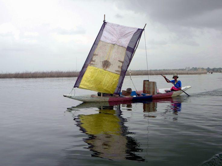 Sailing canoes ply Lake Nokoue near Cotonou, Benin.