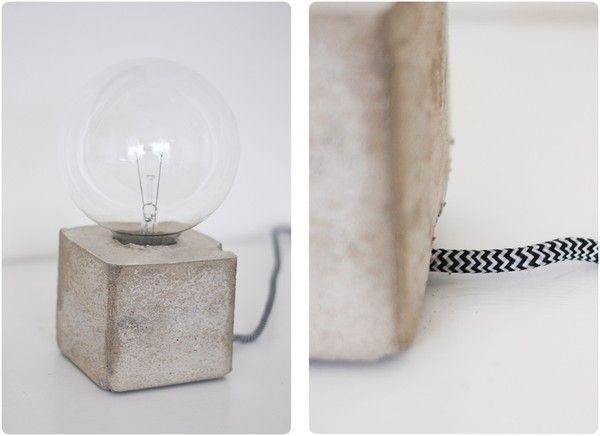"""Lampfot i betong  """"Som form för att gjuta betong använde jag en tom juiceförpackning som jag stoppade ner en toarulle i samt ett rör i botten för sladden."""""""