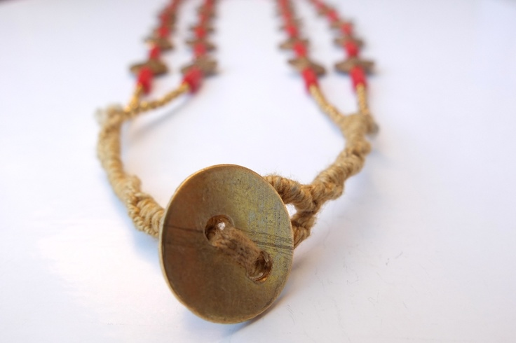 Red fine glass w/ golden brass (small spheres and coins). Two strands in one necklace. Don't miss this detail: you have a kind of coin as clasp. Very fine work.