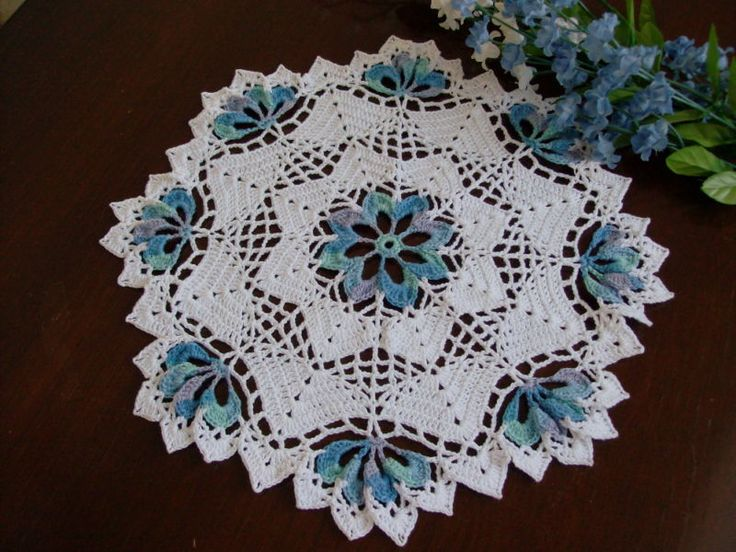 Round crochet doily with blue center and tips.