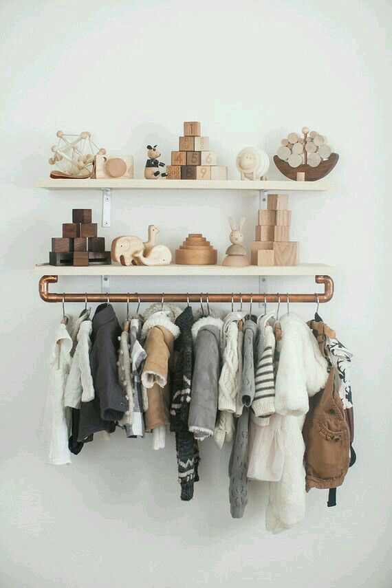 Adorable way to display all your baby jackets! DIY floating shelves with copper piping to hang clothes on.