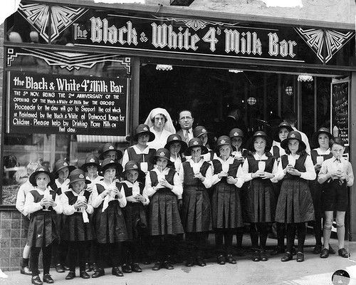 The Black and White 4d Milk Bar in Martin Place, Sydney, 1934. Mick Adams (back row, centre) with children from the Dalwood Children's Health home. The children all have milkshakes, although it was working males who heavily patronised the early milk bars, Mick Adams saw the immediate and long-term benefits of supporting institutions such as the Dalwood Children's Health Home.