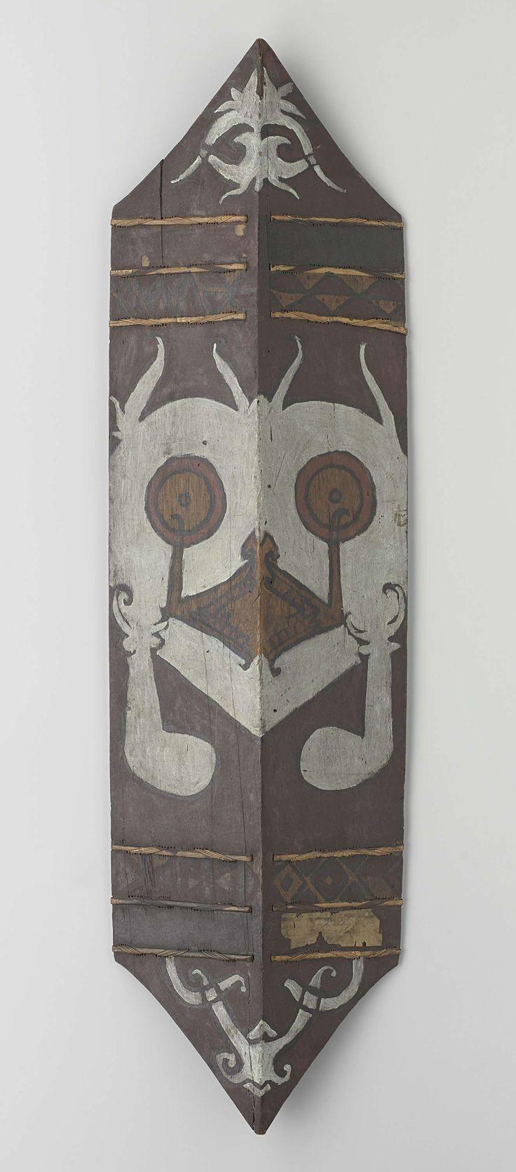 Anonymous | Acehnese shield, Anonymous, before 1877 | Rechthoekig schild aan boven- en onderzijde uitlopend in een punt. In het midden van het schild loopt in de lengterichting een knik naar voren van 15°. Aan de achterkant zit in het midden (in de knik) een handvat. Op de bruine ondergrond is in het midden, over de gehele breedte een symetrische schildering aangebracht. Schildering: een gestileerde kop met 2 ogen en een mond overlopend in een neus. Boven- en onderaan het schild zijn…