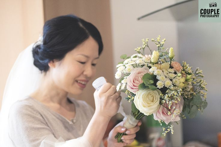 The bride puts the finishing touches to her homemade bouquet. A real D.I.Y wedding. Weddings at Druids Glen Hotel by Couple Photography.