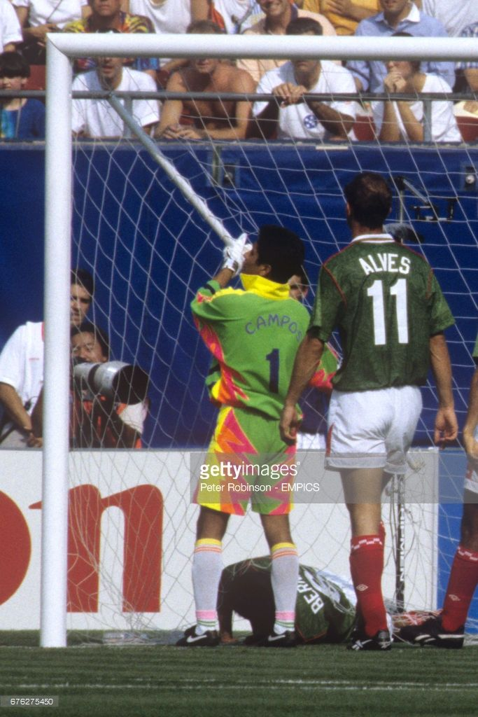 Mexico's Marcelino Bernal (on floor) tries to unravel himself from the goal net after falling into the goal. Mexico Goalkeeper Jorge Campos pulls on the broken stanchion.