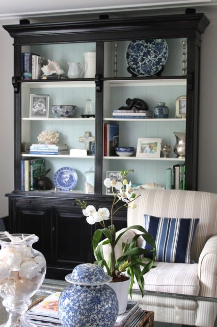 Bookcase Styling - Beautiful Blue & White Living Room. Like the idea of painting the back of the shelves of an antique cabinet to make accessories pop!  6th Street Design School