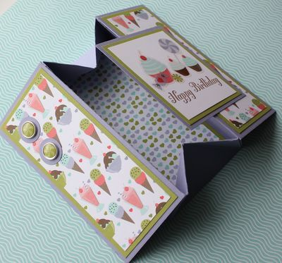"""uses a full 8 1/2 x 11 inch piece of card stock. I scord it at 1 1/2 and 7 in the """"long"""" direction and then 2 1/2, 4, and 8 1/2 in the other direction. Cut off the corners (all four rectangles that measure 1 1/2 x 2). Then make the 1 1/2 inch squares into a tab and create a box. Decorate as you see fit. Then, """"smoosh"""" the box down so it is flattened."""