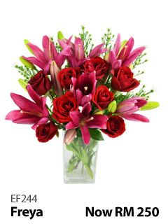 8 red roses & 6 lillies in a glass vase.