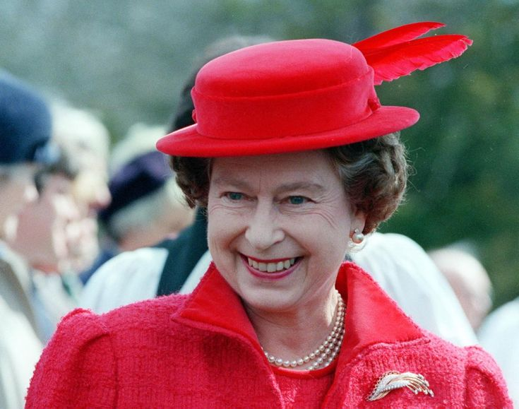 """Queen Elizabeth opts for a matching red coat, hat & the modern ruby brooch after attending morning prayers at the Royal Chapel in Windsor park on April 20, 1986, just days before celebrating her 60th birthday. She is wearing her """"Modern Diamond & Ruby"""" brooch."""