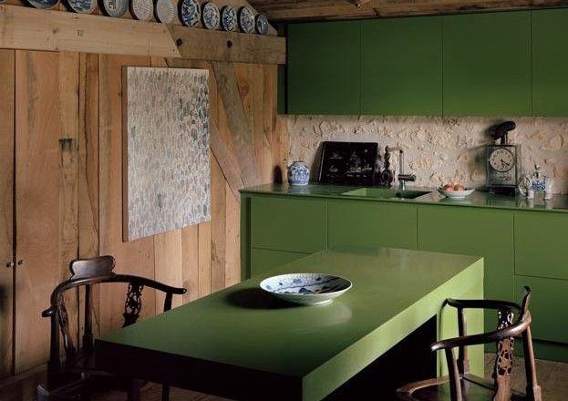 Chalet d'autore Antico e moderno, rustico e design convivono nel fienile di André Dubreuil in Dordogna. Prosegue il gioco dei contrasti anche in cucina dove il modello Gaggenau in Corian verde è circondato da sedute e porcellane cinesi. Puro eclettismo.