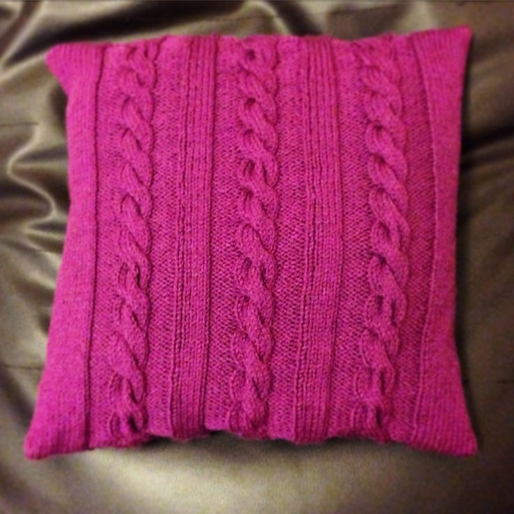 A knitted cable cushion cover. It measures 40cm x 40cm and is actually more purple than pink!