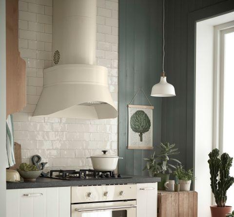 Et hvitt kjøkken med en stor, beige ventilator over en gasstopp og en beige ovn.