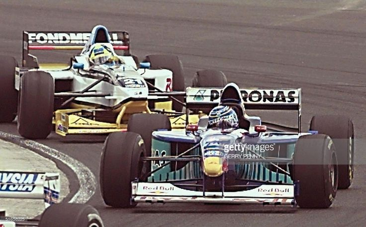 Argentinian F1 driver Norbert Fontana takes a turn followed by Italian Jarno Trulli during the British Grand Prix 13 July at Silverstone.