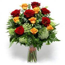 Un mazzo di rose rosse ed arancio, contornato da felce e verde, un caldo regalo per ogni occasione