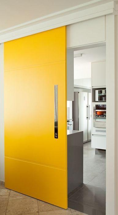 Ярко-желтые раздвижные межкомнатные двери, которые акцентным пятном выделяются на фоне светлого интерьера.