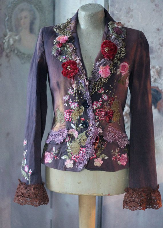 Whimsy baroque inspired cotton jacket, richly reworked/embellished with intricate details, hand dyed in shades of caramel and cold cocoa. The hems are adorned with antique silk lace and vintage textiles, hand sculpted silk, velvet and satin blooms, the jacket has embroidered roses and carnations at hems, at one sleeve and at back. Accentuated with hand beading with shiny champagne shade seed beads. The sleeve ends are trimmed with rust shade lace flounces. The jacket has dusty blue satin...