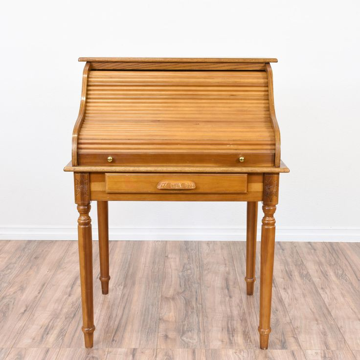This small roll top desk is featured in a solid wood with a a glossy light oak finish and carved tapered legs. This desk is in great condition with 1 drawer, a roll up top and large interior storage with cubbies and shelving! #traditional #desks #hutchdesk #sandiegovintage #vintagefurniture
