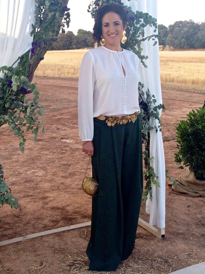 Almudena con conjunto de blusa y pantalón palazzo verde para invitada de boda, cinturón de hojas doradas Verdemint y pendientes dorados de Kenneth Jay Lane - Alquiler de vestidos y accesorios - Dresseos.com