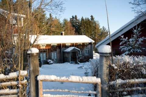 IDYLLISK: Porten leder inn til Karin og Bertils gård Olars, med gjestehytta fra midten av 1700-talet. Til venstre skimtes det nyere huset fra 1939.