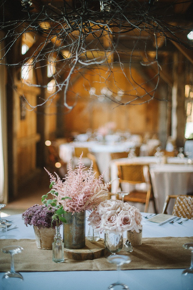 Simple floral table decor on rustic jars; one type of flower in each vase.