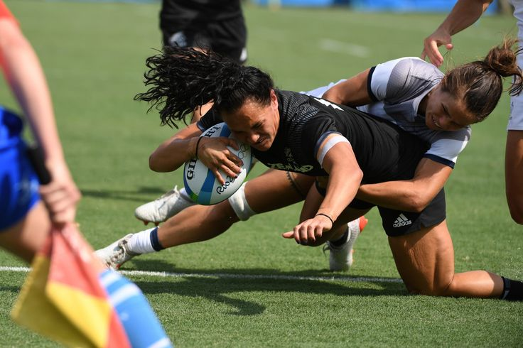 New Zealand's Portia Woodman (C) is tackled by France's Camille Grassineau as she scores a try in the womens rugby sevens match between New Zealand and France during the Rio 2016 Olympic Games at Deodoro Stadium in Rio de Janeiro on August 7, 2016. / AFP / Pascal GUYOT