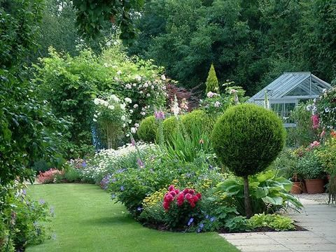 Cottage & Country Gardens - love those lollipop/standards which make a welcome contrast to the blousy planting.
