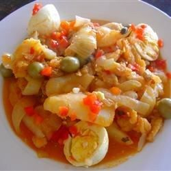 Soaked salt cod is layered with potatoes, eggs, golden raisins, capers, and roasted red peppers, then simmered in a white wine-tomato sauce.