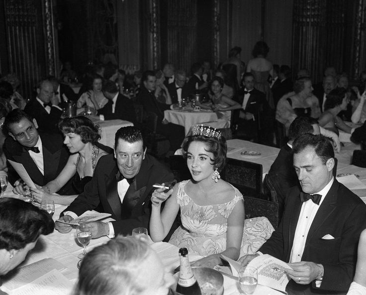 Actress Elizabeth Taylor, decked out in a glittering tiara and large drop earrings, chats with French comedian Fernandel as they attend the St. Valentine's Ball given by the American community in Paris, Feb. 14, 1958. At right is Ms. Taylor's husband Mike Todd. (AP Photo)
