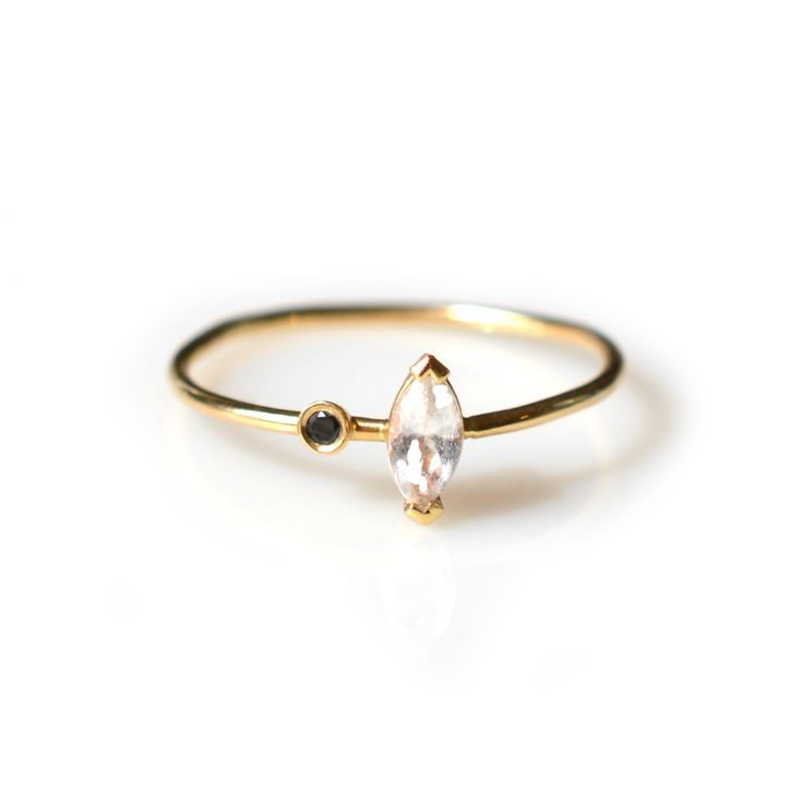 -solid 14kt gold -marquise cut white topaz -3pt black diamond -1mm ring band A perfectly dainty stacking ring with a uniquely set white topaz and black diamond. (this ring is made to order, so please
